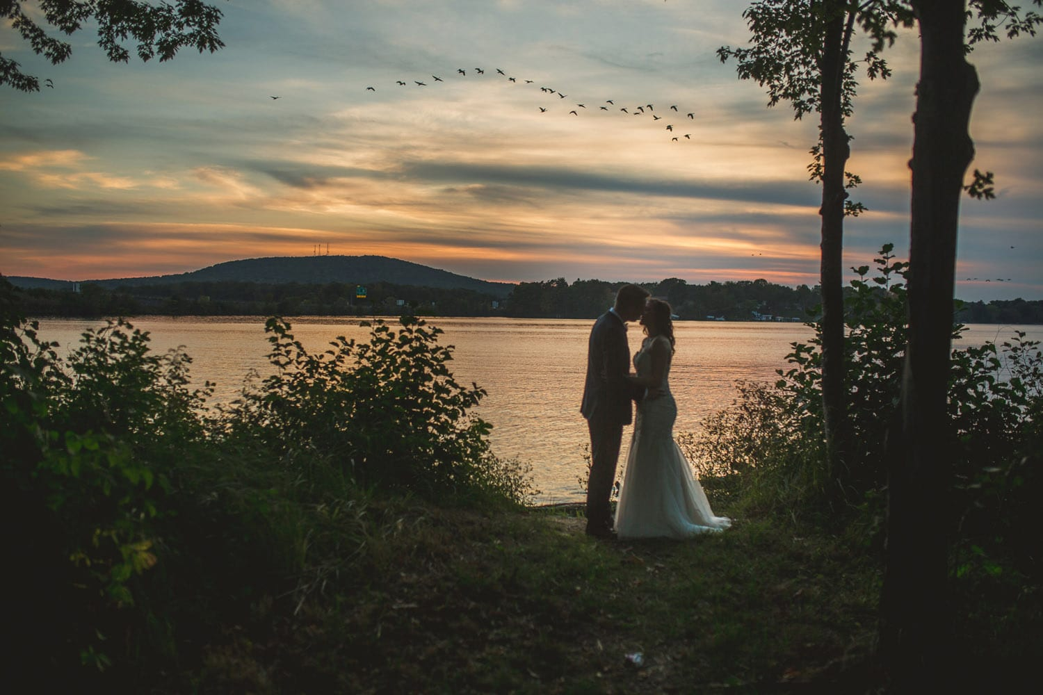 bride and groom on lake with birds flying by
